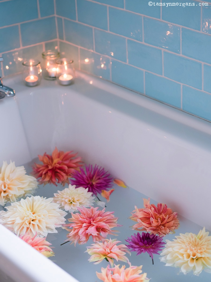 Aqua bathroom tiles and flowers in the bath