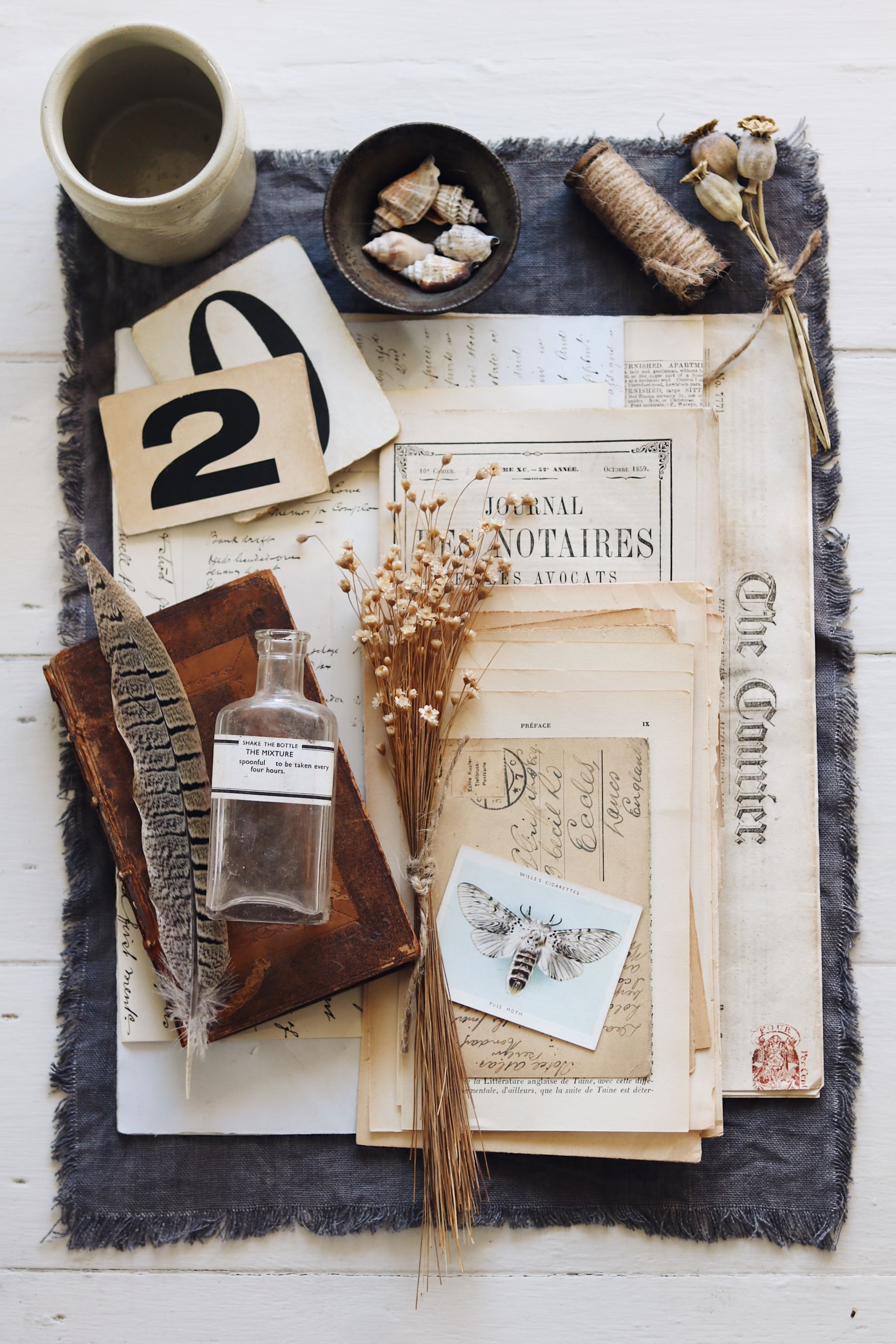 Flat lay of vintage paper ephemera and bottle