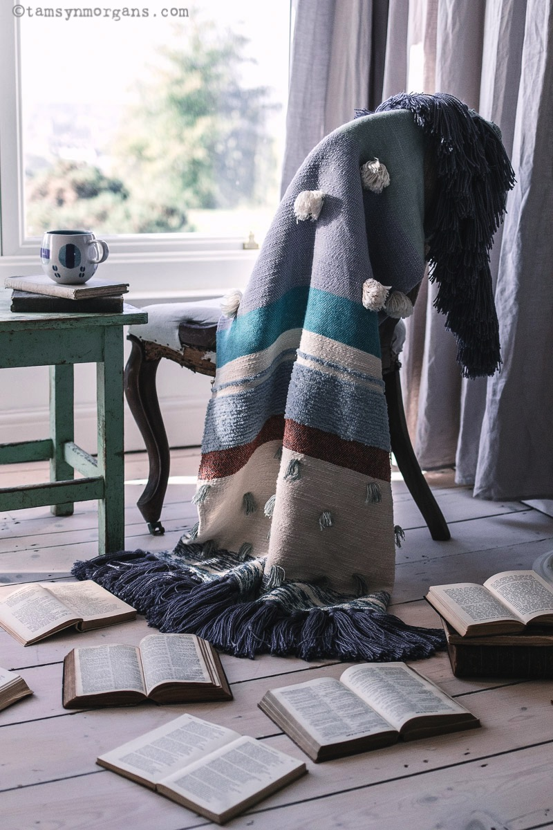 Cosy chair and blanket with vintage table and cup of tea.