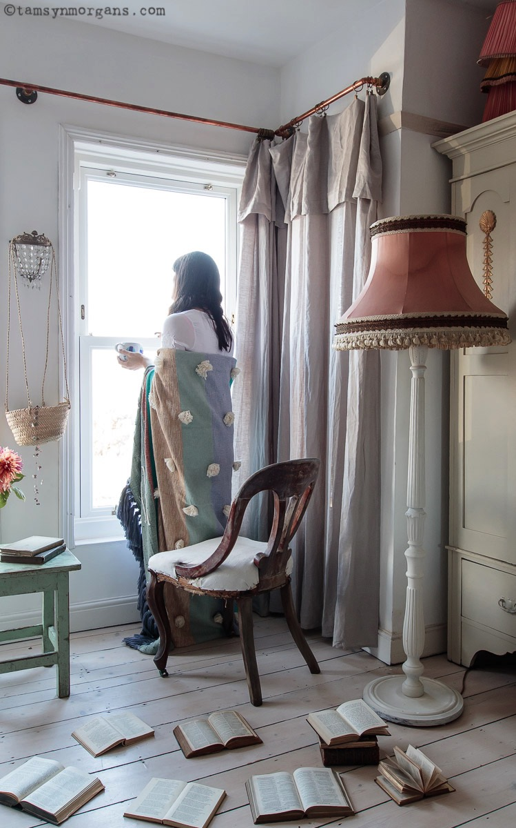Woman looking out of a window, with a blanket and mug of tea.