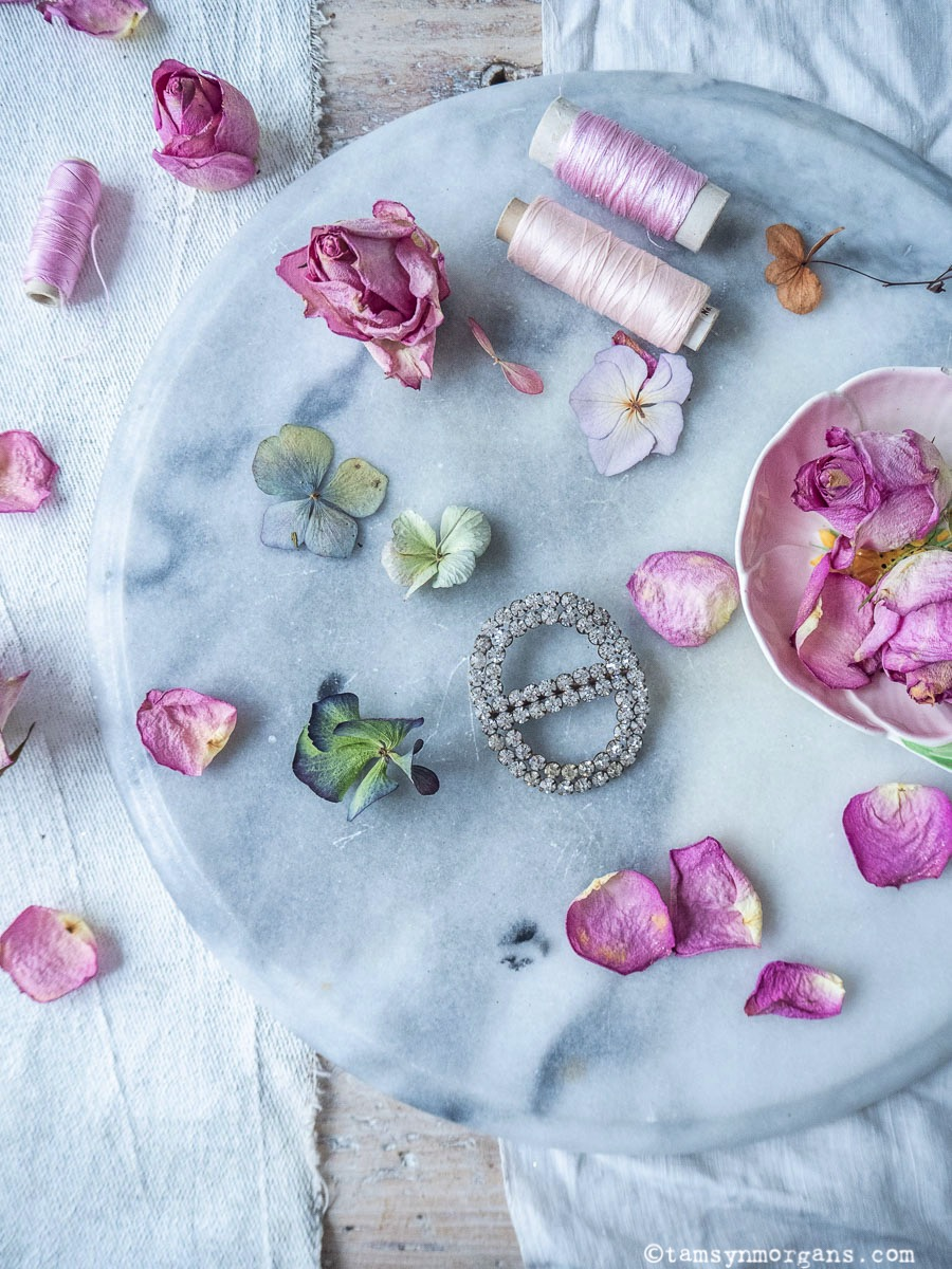 Rose petals and cotton reel flatlay